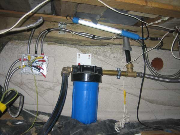 Чёрный с синим трубопровод подводящий воду из колодца в подпол дома.  Далее синяя ёмкость это фильтр воды.
